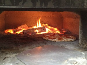 Pizza bubbling right by the fire. Spectacularly nice on a strangely cold spring day.